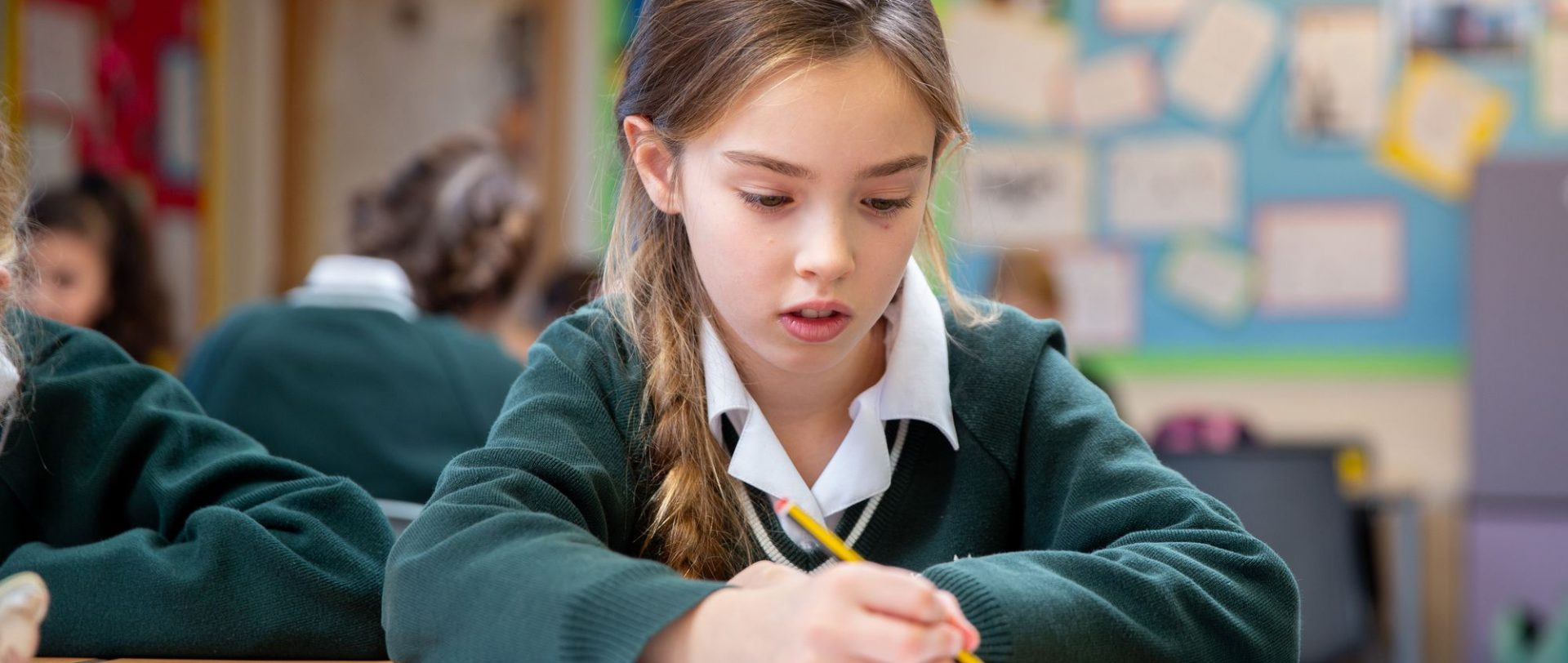 school girl writing with a pencil
