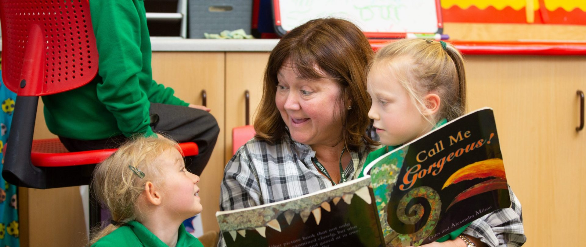 teacher reading a story to early years students