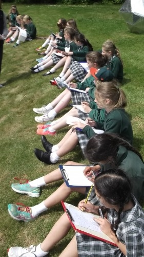 children sitting in a row outside holding clipboards