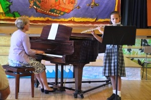 girl playing flute next to a woman playing piano