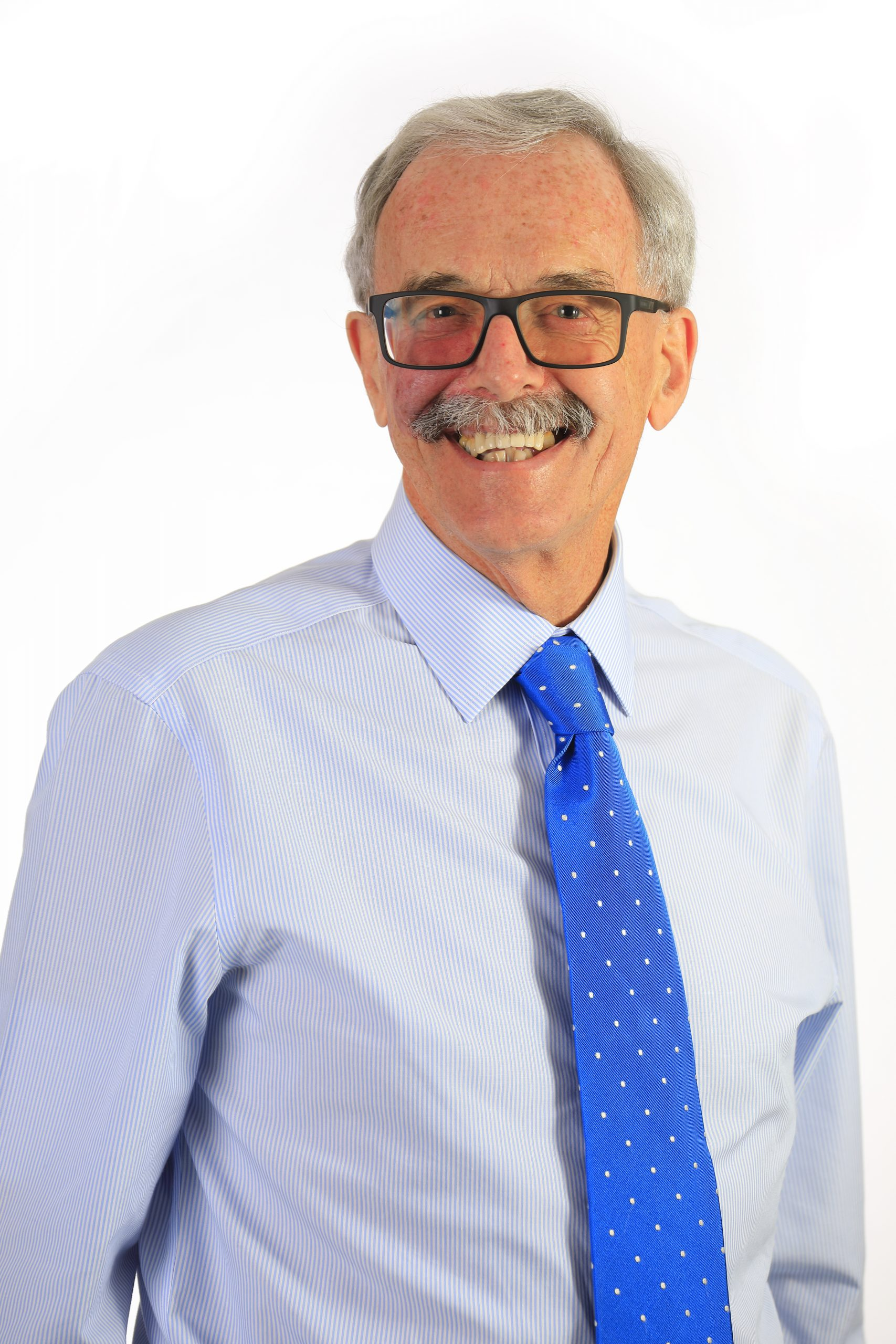 Photo of a smiling grey haired man with a moustache, glasses and smart shirt and tie