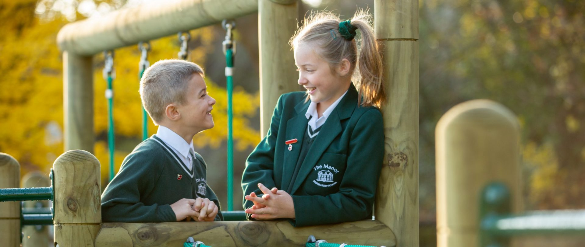 two children standing on a climbing frame