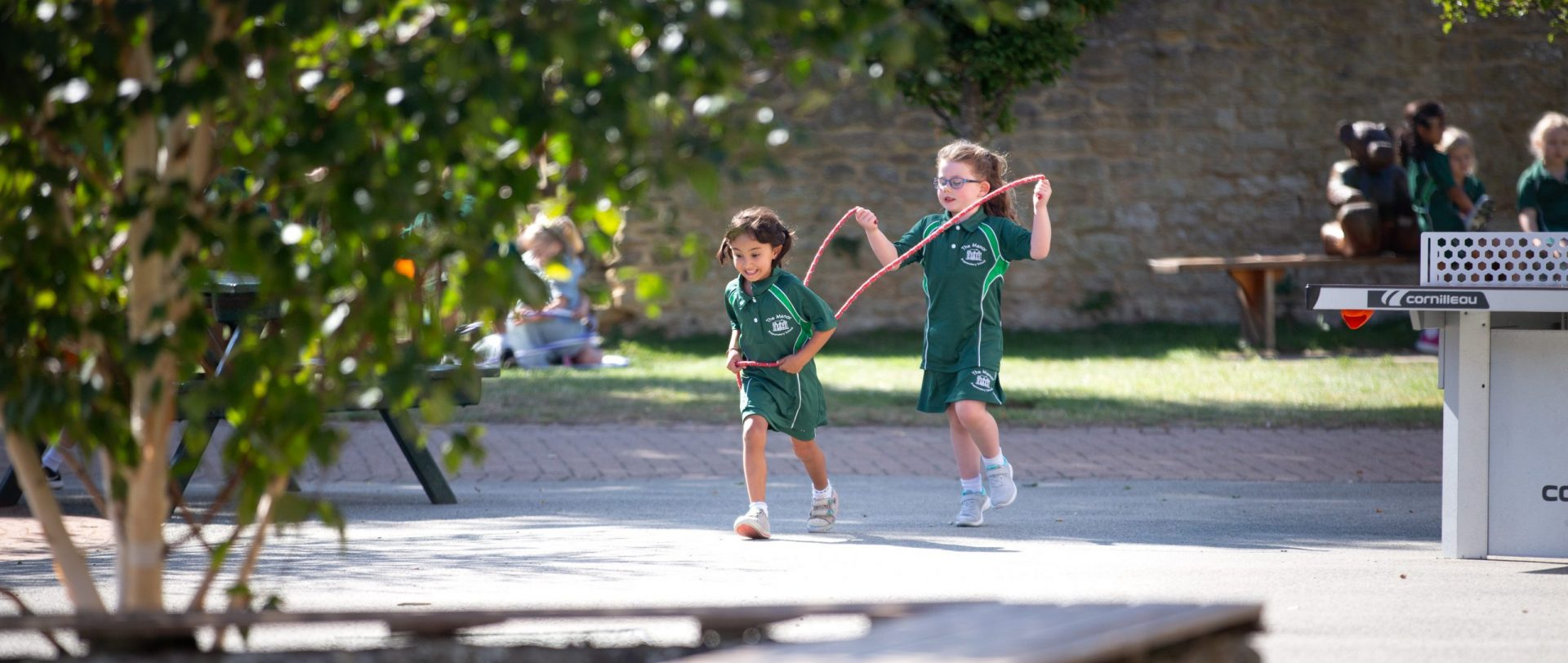 two young girls outside with a skipping rope