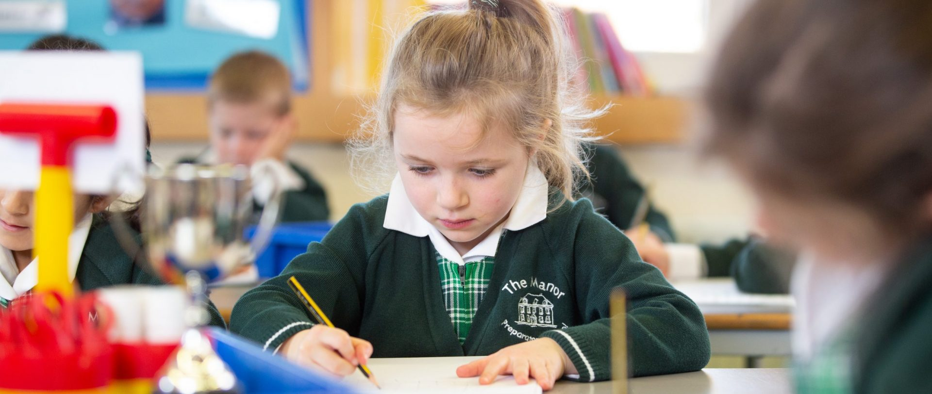 young child writing in a classroom