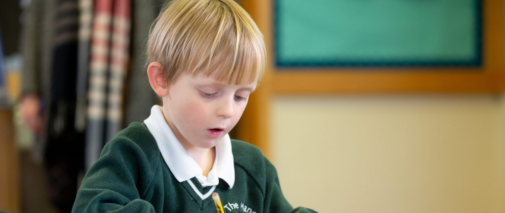 young child writing with a pencil at school